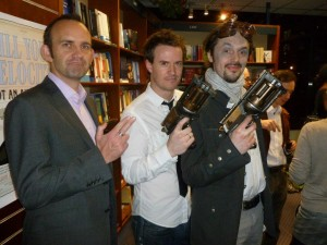 A photograph: Mark de Jager, James Long and Den Patrick hold up steampunk style guns